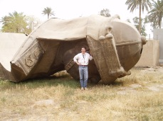My friend Dave stands next to one of the structurally decapitated heads of Saddam Hussein. Baghdad, Spring 2004.